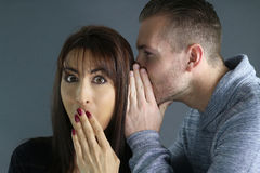 Young man telling a secret to a woman Stock Photo