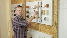 A young man tells and shows the switch sockets and wires of different colors and shapes. Samples are presented on a stock footage