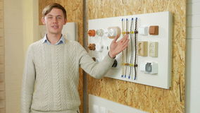A young man tells and shows the switch sockets and wires of different colors and shapes. Samples are presented on a stock video footage