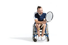 Young man with tennis racquet sitting in wheelchair and looking away Stock Photos