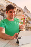 Young man on terrace with tablet and wine Stock Photos