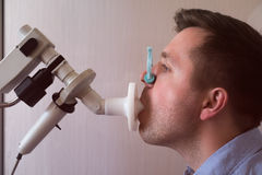 Young man testing breathing function by spirometry. Medical test stock photo