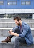 Young man text messaging on mobile phone Stock Photography