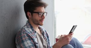 Young man text messaging on mobile phone stock video footage