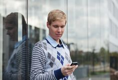 Young man texting. Young handsome man texting with his cellphone while standing next to glass reflective wall Stock Photos