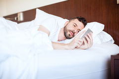 Young man texting in bed. Good looking young man using his smartphone and texting while lying on his bed stock images