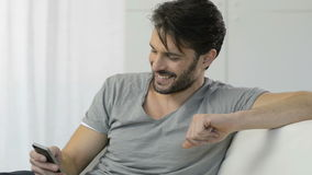 Young Man Texting On Cellphone. Happy Young Man Sitting On Sofa Sending Text On Cellphone. Smiling man with beard in casual typing on his smartphone and