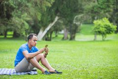 Young man texting on the cellphone. Portrait of young man using mobile phone in the park Royalty Free Stock Image
