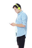Young man texting on his phone and listening to music. Isolated on white Stock Image