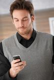 Young man texting on mobile phone Stock Image