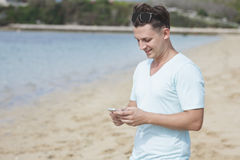 Young man texting on mobilephone at the beach Royalty Free Stock Image