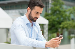 Young man texting on mobilephone Stock Photography