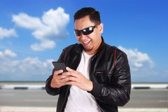 Young Man Texting Reading Chatting on His Phone Happy Smiling Ge Stock Image
