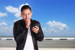 Young Man Texting Reading Chatting on His Phone Sad Gesture. Attractive young Asian man wearing black leather jacket reading texting chatting on his phone, sad Royalty Free Stock Images