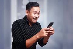 Young Man Texting Reading Chatting on His Phone, Smiling Happy. Attractive young Asian man reading texting chatting on his phone, smiling happy laughing stock photography