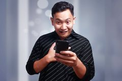 Young Man Texting Reading Chatting on His Phone, Smiling Happy. Attractive young Asian man reading texting chatting on his phone, smiling happy laughing Stock Image