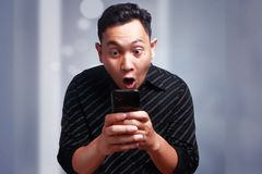 Young Man Texting Reading Chatting on His Phone, Surprised Happy. Attractive young Asian man reading texting chatting  on his phone, smiling happy laughing Royalty Free Stock Photo