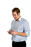 Young Man Texting with Smart Phone. Portrait of a content young man texting on a smart phone. Isolated on white Stock Photos