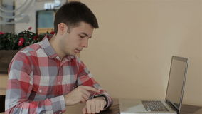 Young man texting on smartphone in cafe and using smartwatch stock video footage