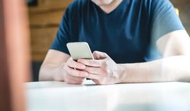 Young man texting with smartphone. Guy using mobile phone. stock image