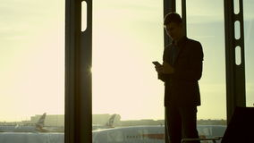 Young man is texting by using his smartphone in airport stock footage