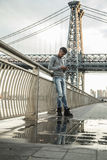 A young man texts infront of New York City`s Williamsburg Bridge Stock Photo