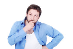 Young man thinking. Young white model in blue shirt thinking Royalty Free Stock Images
