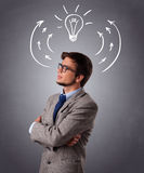 Young man thinking with arrows and light bulb overhead Royalty Free Stock Images