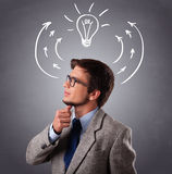 Young man thinking with arrows and light bulb overhead Stock Photography
