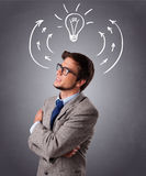 Young man thinking with arrows and light bulb overhead Royalty Free Stock Photo