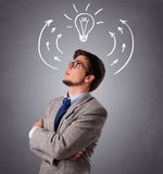 Young man thinking with arrows and light bulb overhead Royalty Free Stock Photos