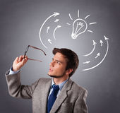 Young man thinking with arrows and light bulb overhead Royalty Free Stock Image