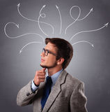Young man thinking with arrows overhead Stock Photo