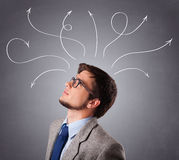 Young man thinking with arrows overhead Stock Photography