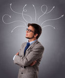 Young man thinking with arrows overhead Royalty Free Stock Photo