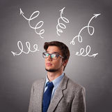 Young man thinking with arrows overhead Royalty Free Stock Images