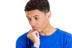 Young man thinking daydreaming, looking downward, chin on fist Royalty Free Stock Images