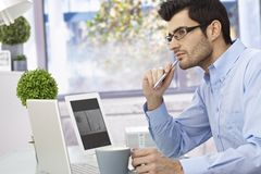 Young man thinking at desk Stock Photo