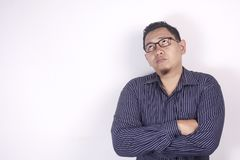 Young Man Thinking Expression, Looking to The Side. Young Asian man wearing blue shirt thinking gesture, looking to the side. Close up body portrait against stock photography
