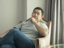 Young Man Thinking Expression, Looking to The Side. Young Asian man wearing casual grey shirt thinking, looking to the side. Close up body portrait indonesian stock photo