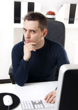 Young man thinking in front of his computer Royalty Free Stock Images