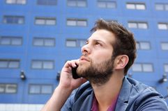Young man thinking with mobile phone Royalty Free Stock Photo