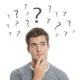 Young man thinking. Pensive young man with question marks Royalty Free Stock Photos