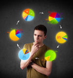 Young man thinking with pie charts circulation around his head Stock Photo