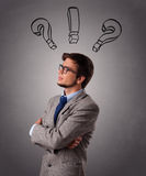 Young man thinking with question marks overhead Stock Image