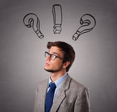 Young man thinking with question marks overhead Stock Photos