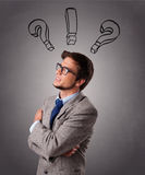 Young man thinking with question marks overhead Stock Images