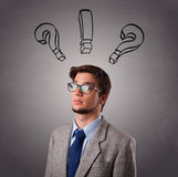 Young man thinking with question marks overhead Royalty Free Stock Images