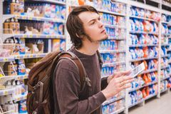 Young man is thinking about shopping with a tablet selects household chemicals in a supermarket.  Stock Images