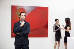 Young man thinking with two women talking in background in art gallery Royalty Free Stock Photos